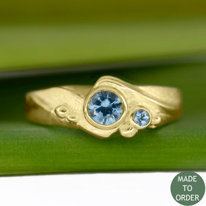 This ring, Rising Tide, embodies the motion and the balance of the sea. The ocean-blue Montana Sapphires are encircled by wave formations sculpted in 18K yellow gold. Around the gemstone, the metal is hand-textured creating a sparkling sand-like finish along with sea foam bubbles that dance across the wave. The band is finished with a high polish.