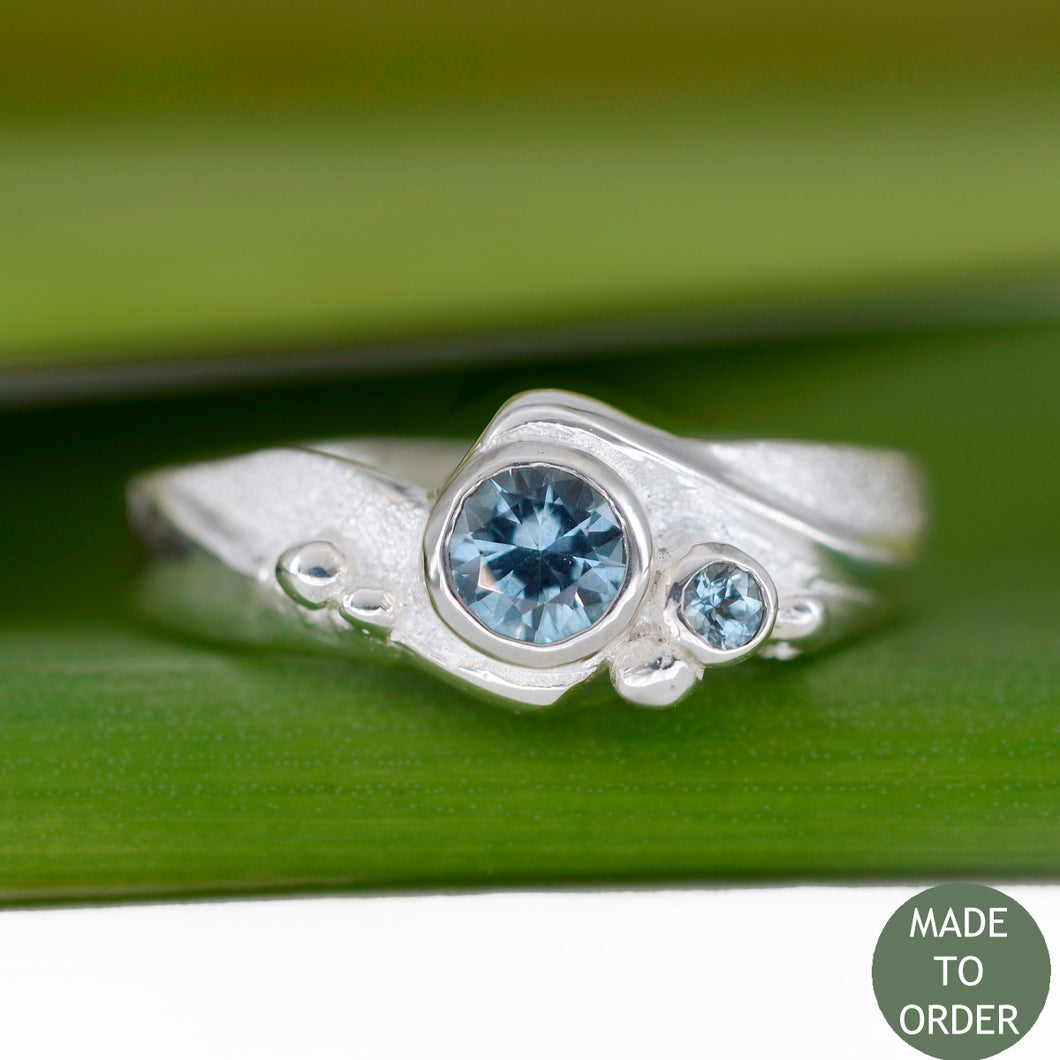 This ring, Rising Tide, embodies the motion and the balance of the sea. The ocean-blue Montana Sapphires are encircled by wave formations sculpted in silver. Around the gemstone, the metal is hand-textured creating a sparkling sand-like finish along with sea foam bubbles that dance across the wave. The band is finished with a high polish.