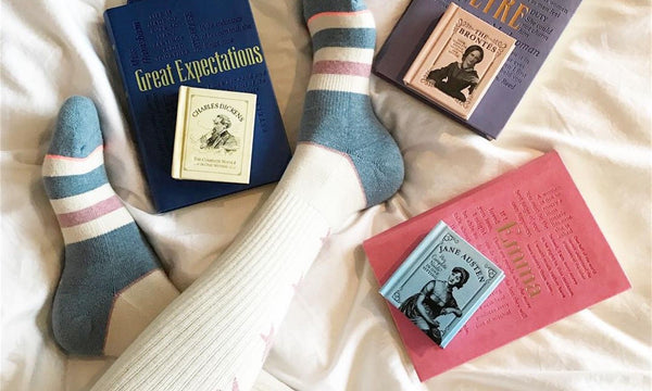 womans feet with 6 books. read before sleep