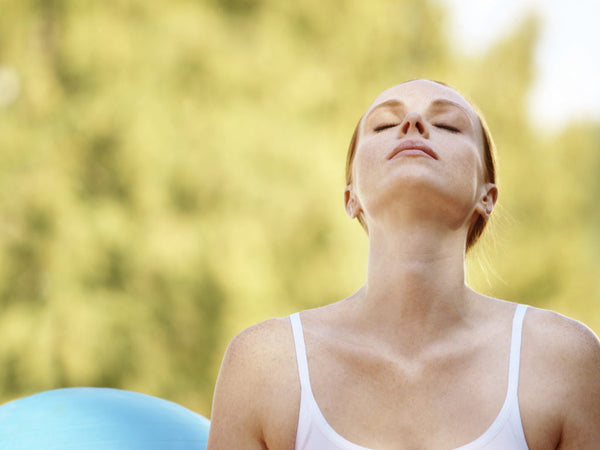 Woman outside breathing with eyes closed while looking to the sky and sun