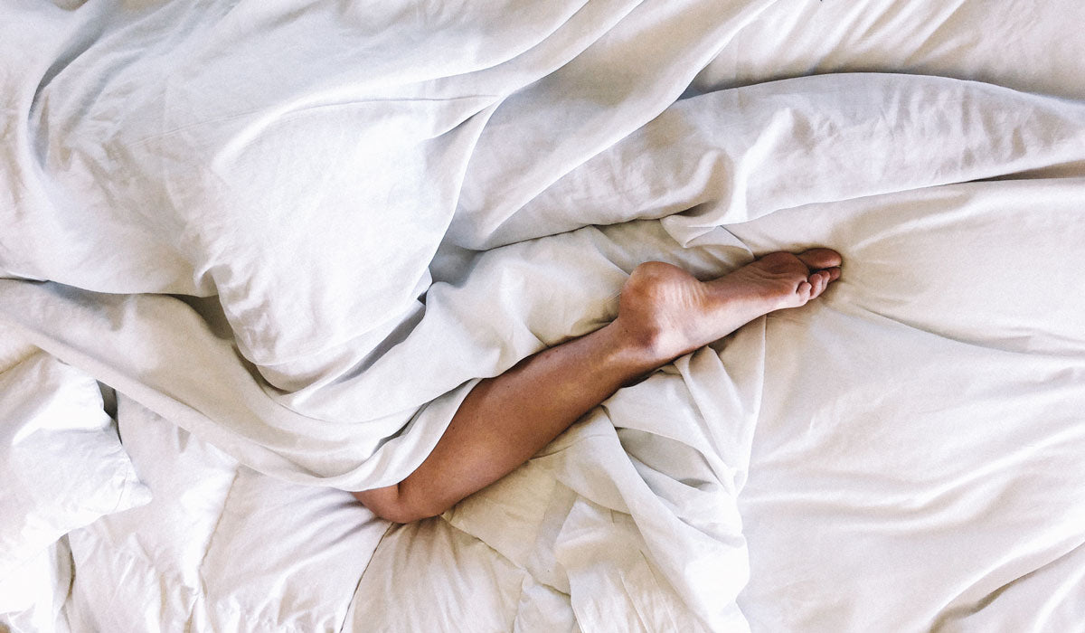 ageing skin womans leg in white bed sheet