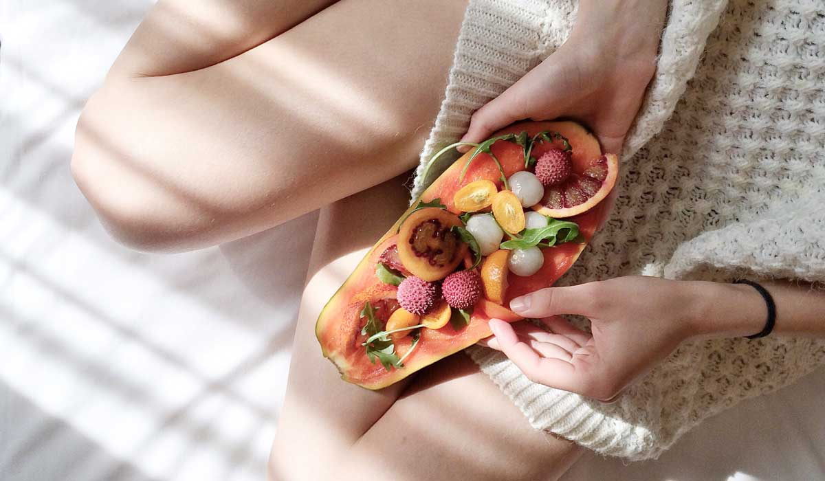 conscious choices person holding fruits in bed