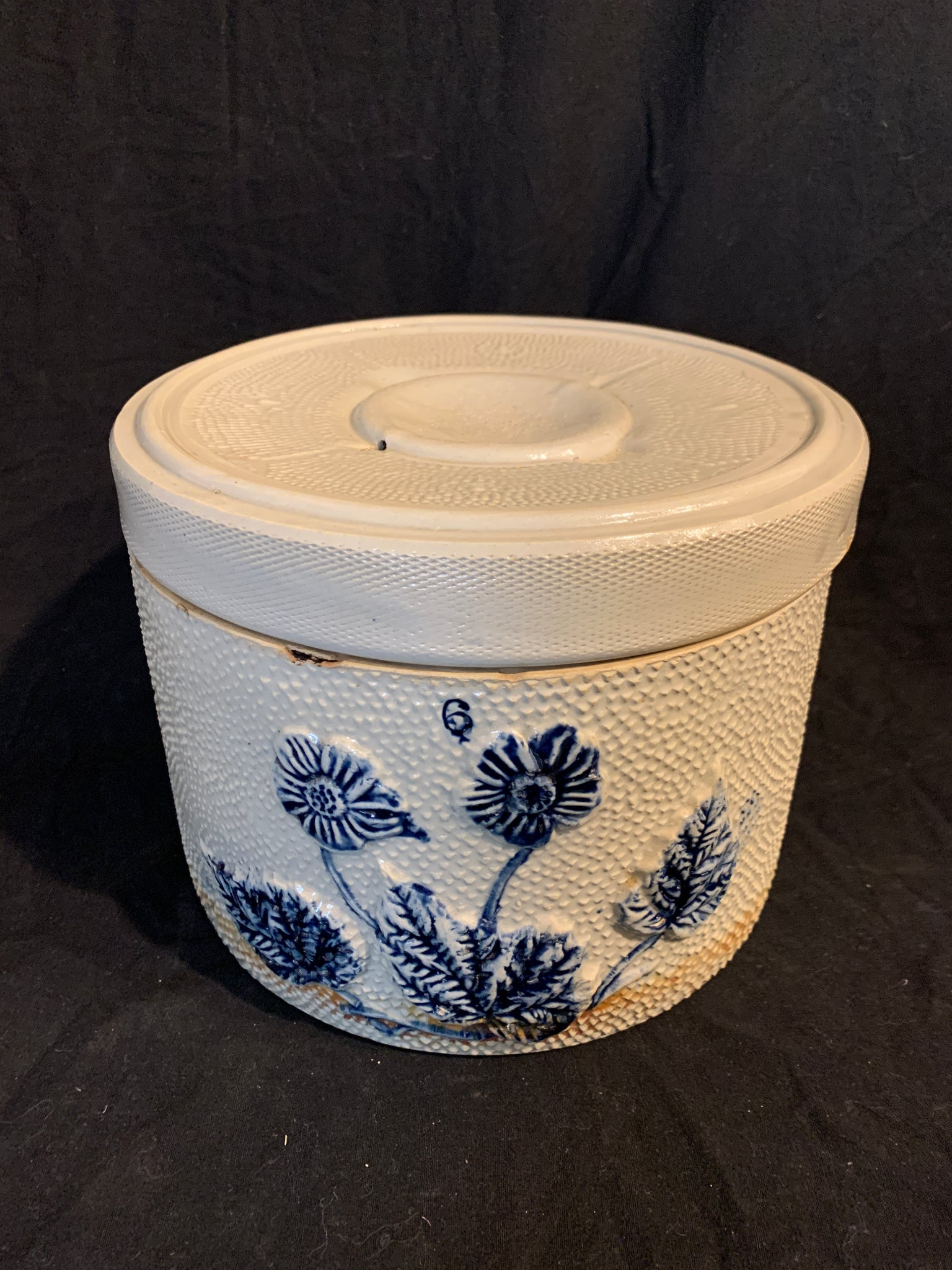 Circa 1870 Country American stoneware covered butter crock with raised floral and leaf design on a stipple texture ground