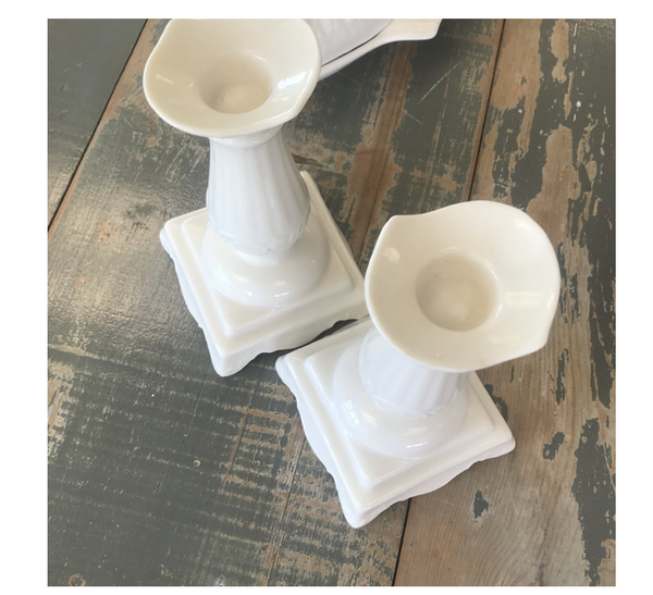 Beautiful pair of white ceramic porcelain candlesticks on a square base. Modeled after white regal ionic-Greek columns.
