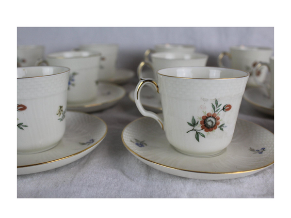 Twelve Royal Copenhagen demitas cups and saucers. Ribbed molded body with floral design and gilt band.