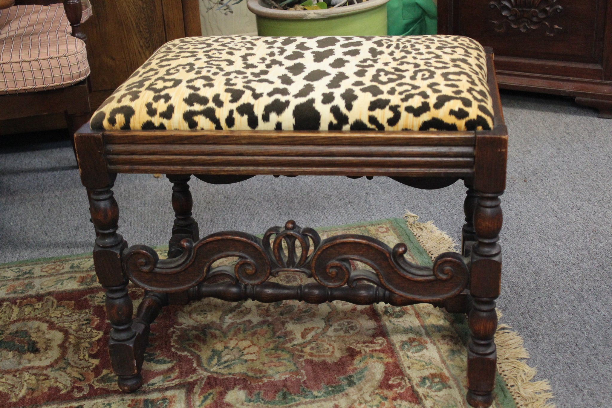 "Jacobean Style Carved Oak Bench. This early 20th Century reproduction bench is in good condition with minor wear.  It is English made oak wood with an upholstered top, and is 24""x18""x19"" tall."