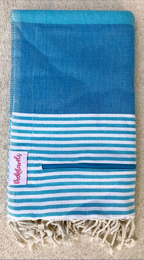 Andaman Pocketowel features sky-blue, turquoise and white stripe for a cool coastal vibe. Pocketowels are large beach towels with pockets