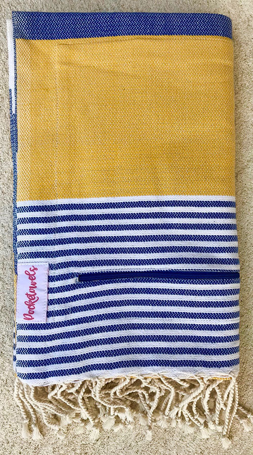 Arambol Pocketowel is navy and yellow stripe for a coastal vibe. Pocketowels are large beach towels with pockets