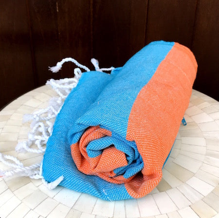 Our SunSea Turkish Towel is orange and blue stripes, and rolls up so small!