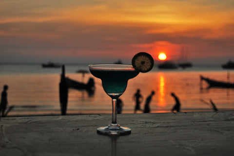 In the foreground, a wooden table atop which, a cocktail glass filled with a green drink, garnished with a wedge of lemon. In the background, a beach party set against the setting sun at a beach.