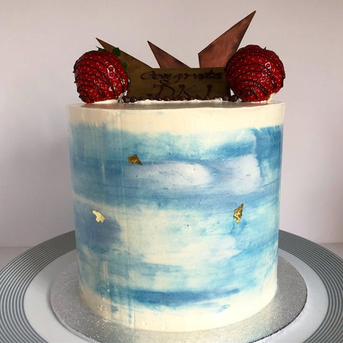 A blue and white rtall cake waiting to be sliced up!