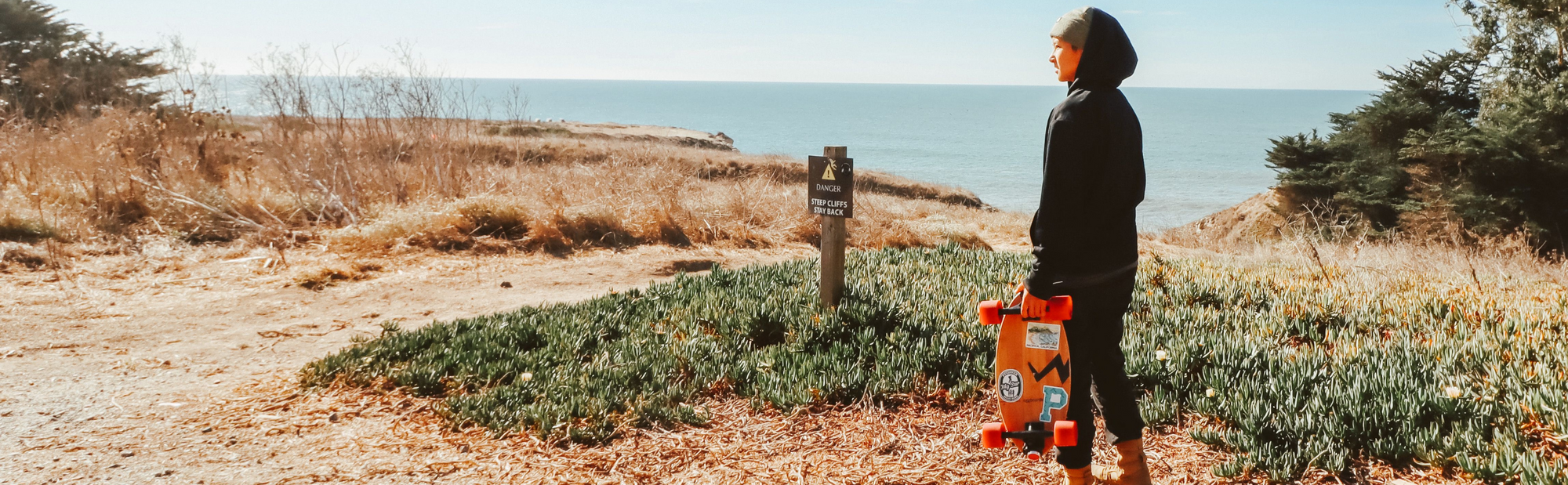 Girl With Eggboard Skateboard In Nature Overlooking The Ocean