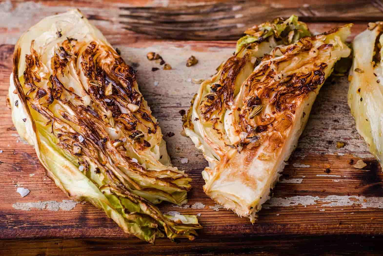 Two charred wedges of cabbage on a wooden background