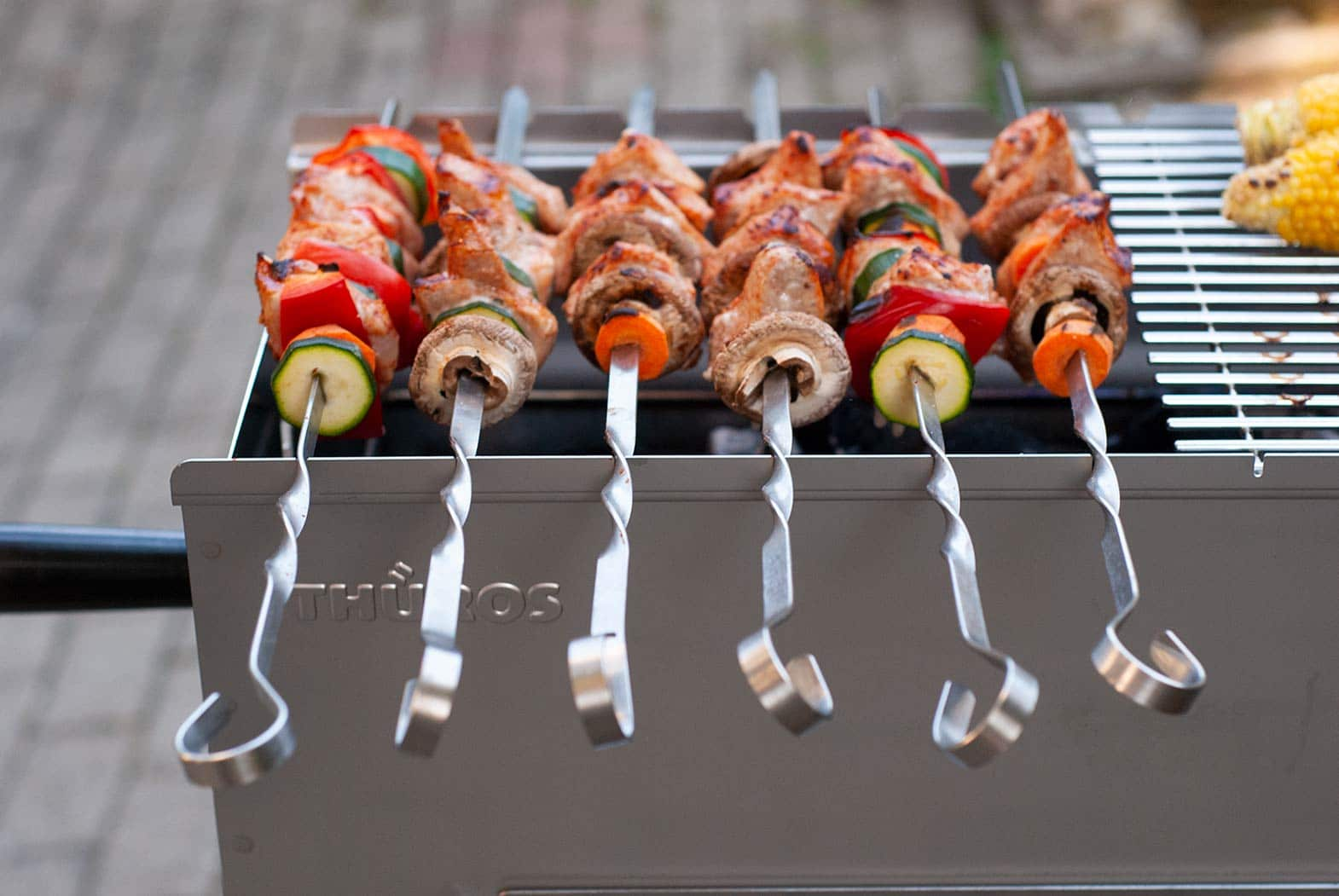 Meat and vegetable skewers on a grill