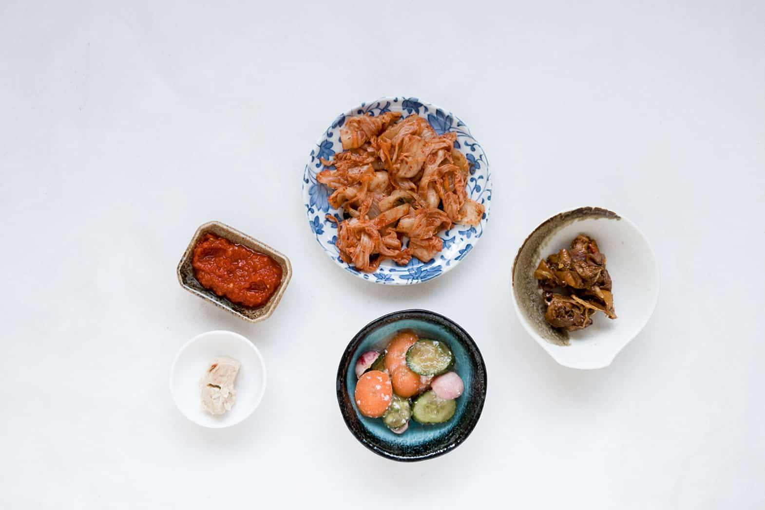A grey background with bowls of kimchi and fermented food