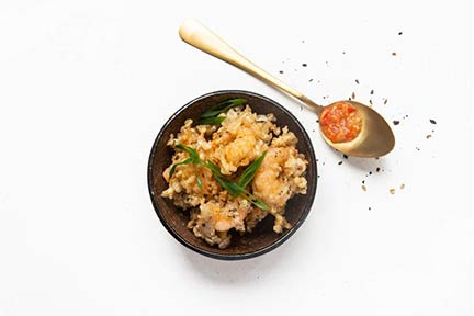 A bowl filled with crispy fried prawns sprinkled with black pepper