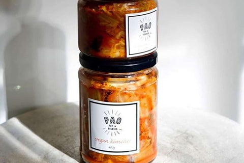 Two jars of kimchi with white labels on the front