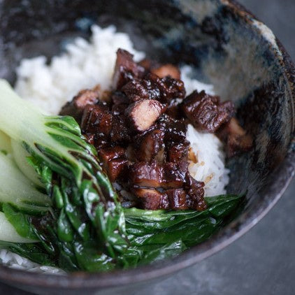 Pork slices in a bowl with rice and pak choi