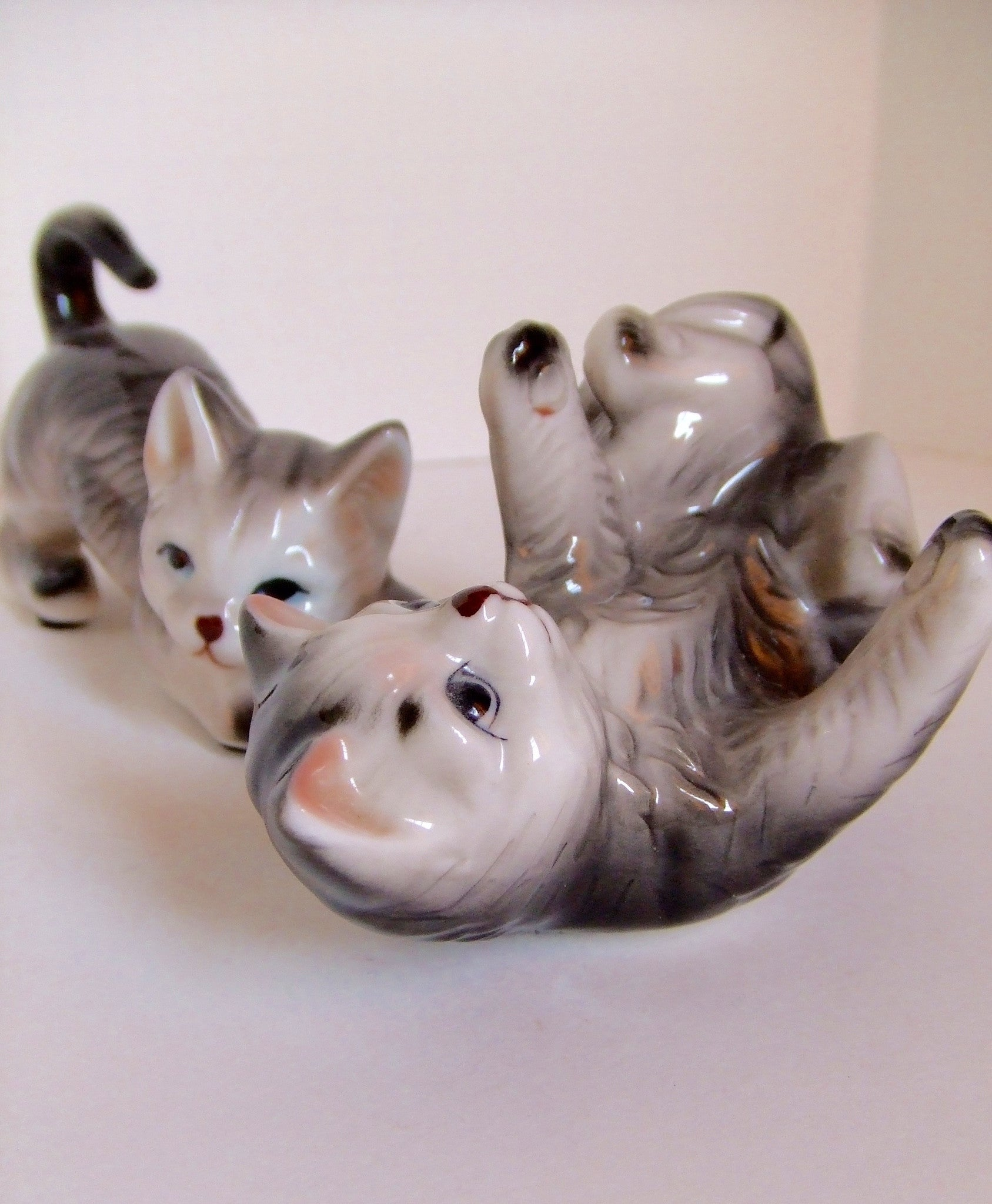Pair of playful furry kitten figurines.