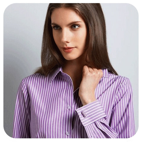 Woman wearing cufflinks on purple and white striped double French cuff shirt