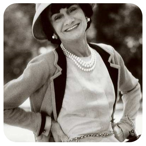 Coco Chanel wearing cufflinks on a white blouse, blazer and dress.