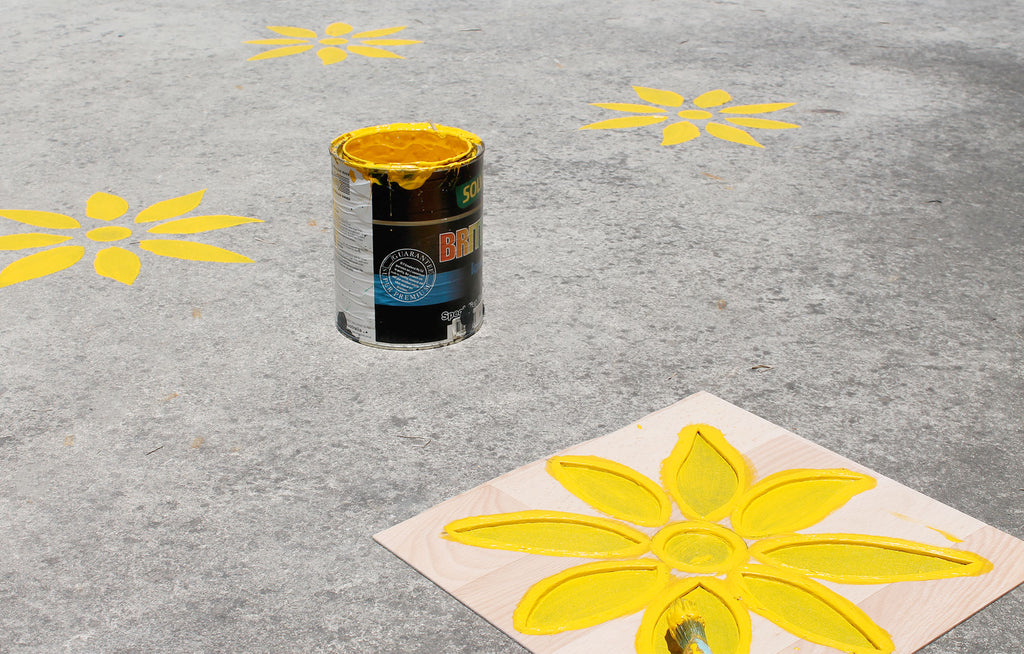 Bright yellow diy daisy stencil painted on cement