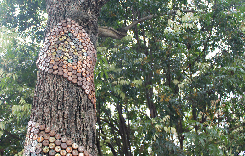 Public art in Nimbin Australia. Tree decorated with bottle caps