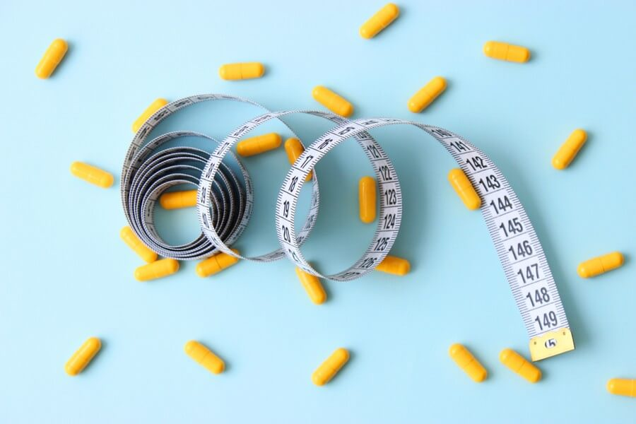 An image showing a tape measure and fat burner pills