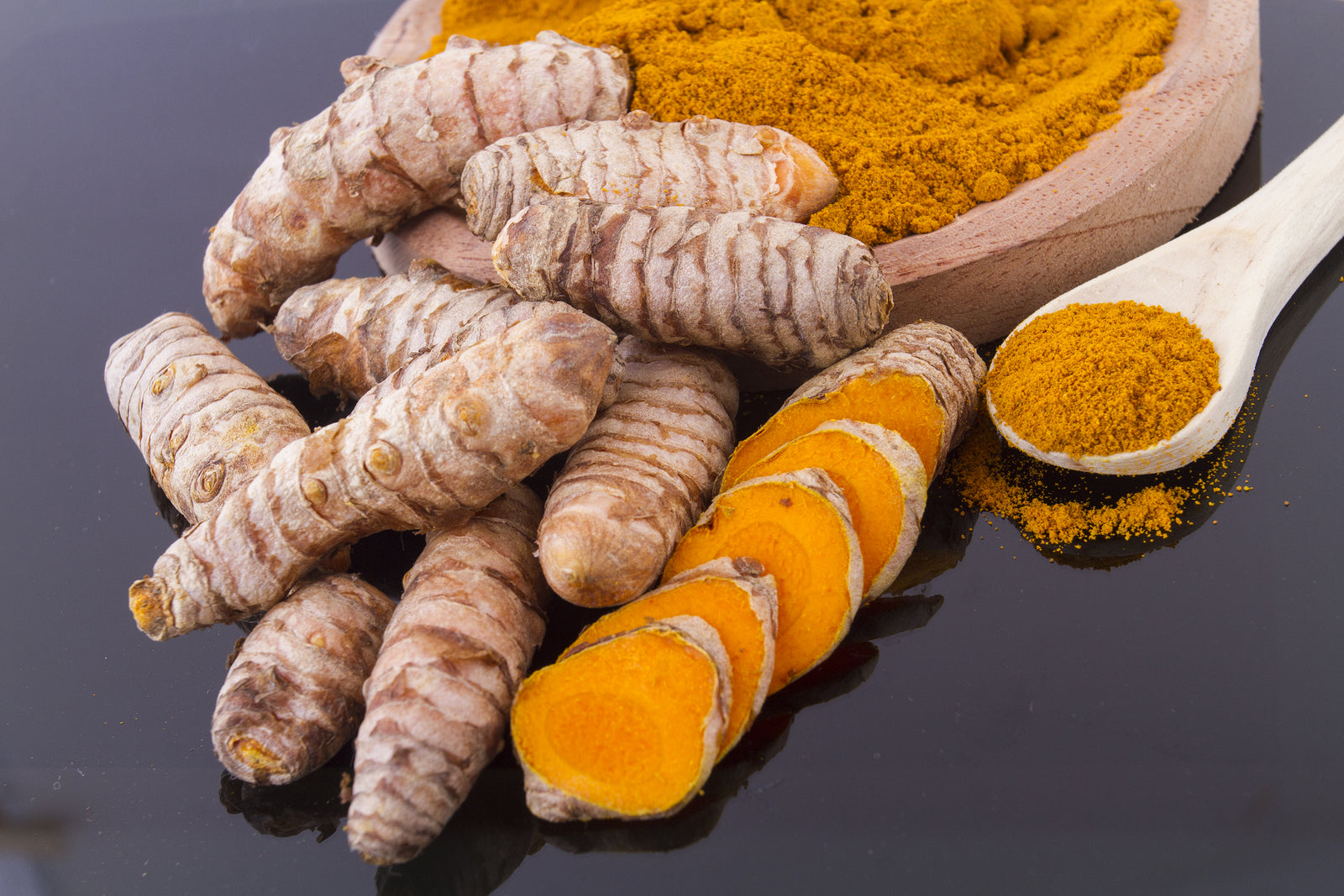 Curcumin pictured in its many different forms such as the root and powder as a joint support supplement