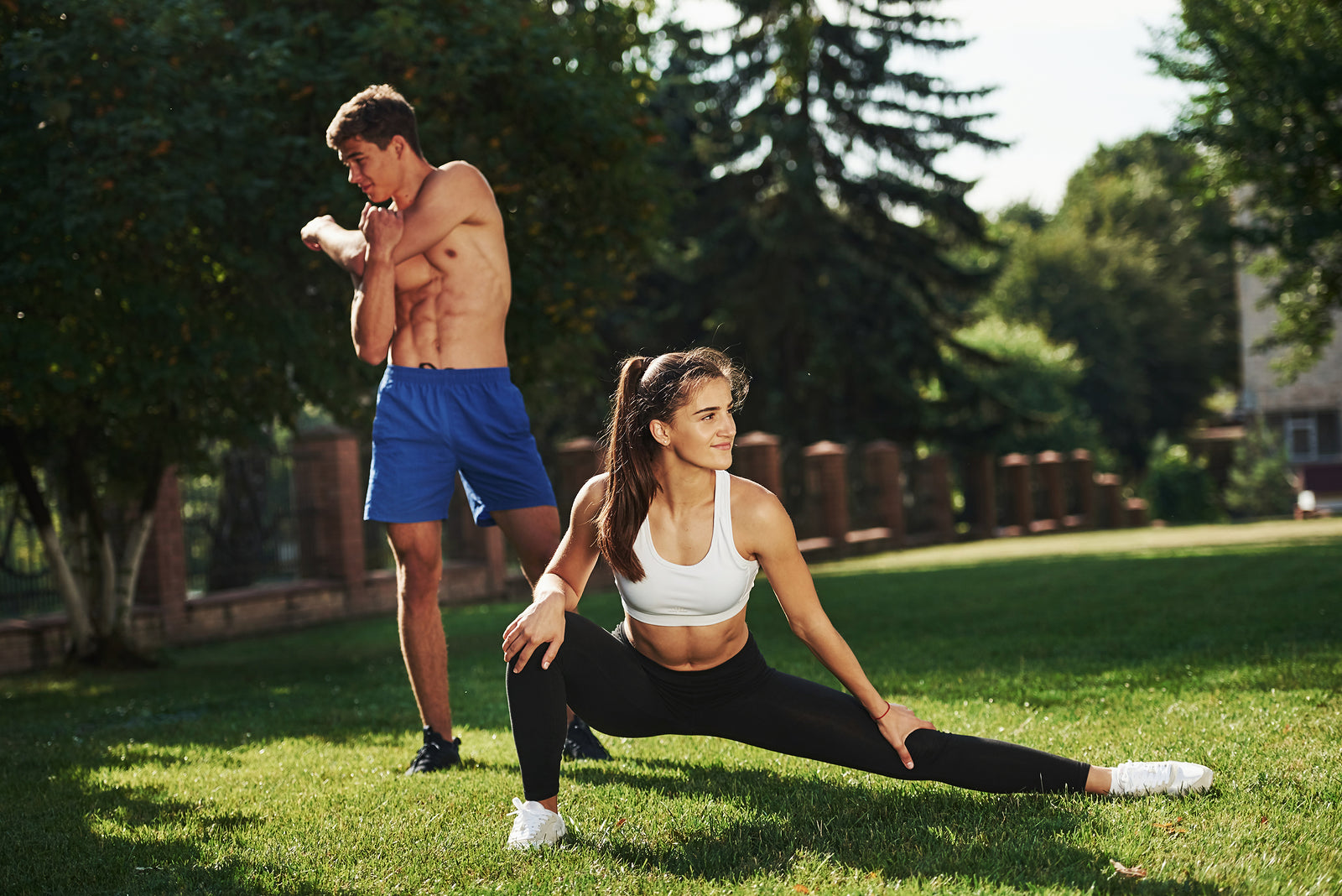 A man and woman stretching off showing abs