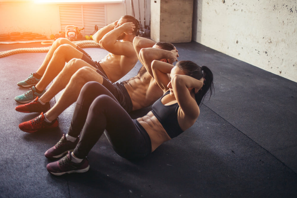 2 men and a female working their abs for fat loss during a workout