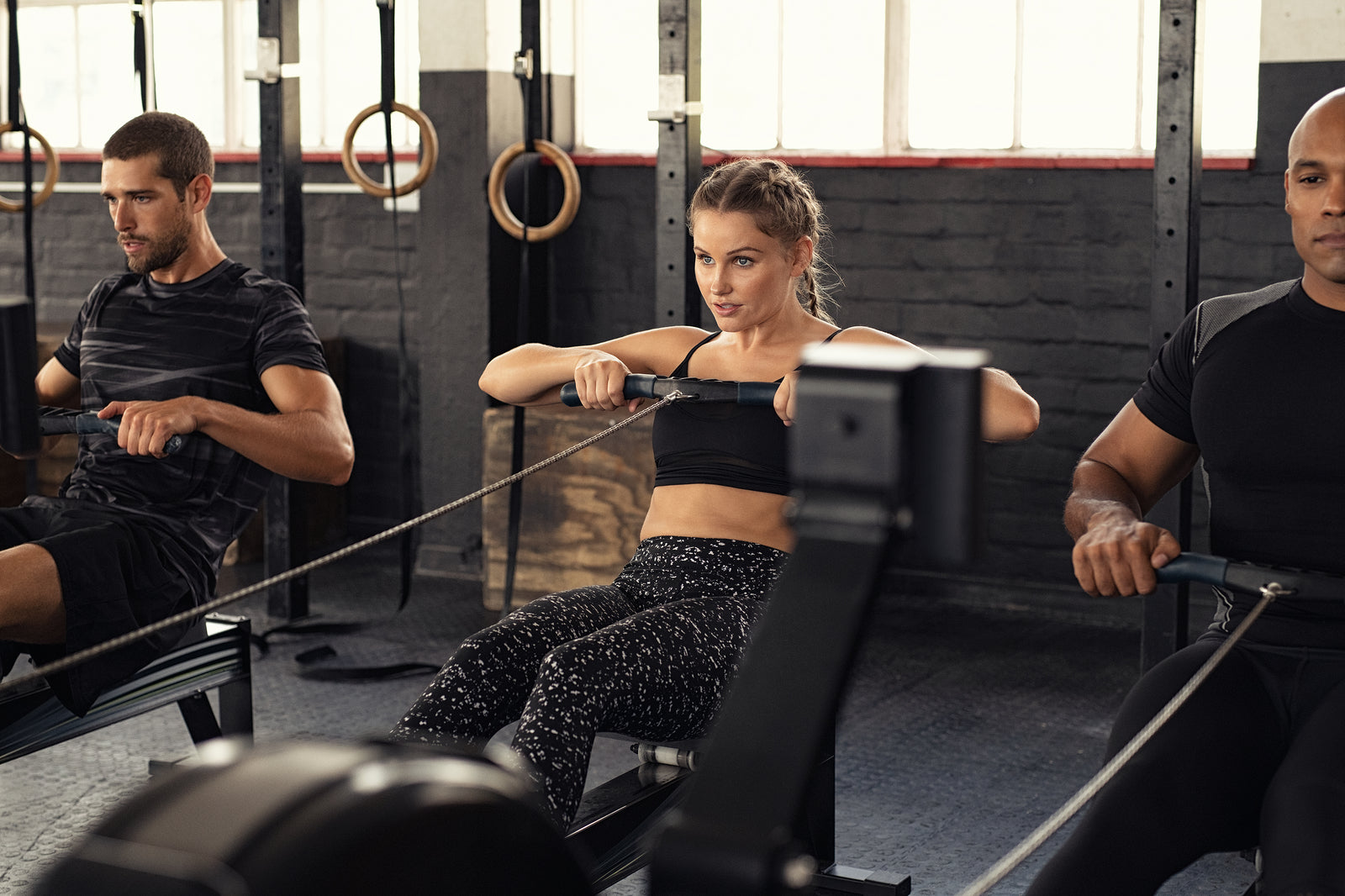 Men and women workout on the rowing machine to get results