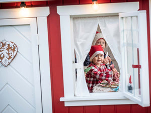 Kids decorating gingerbreads inside of the red Kids Playhouse Nordic Nario by WholeWoodPlayhouses