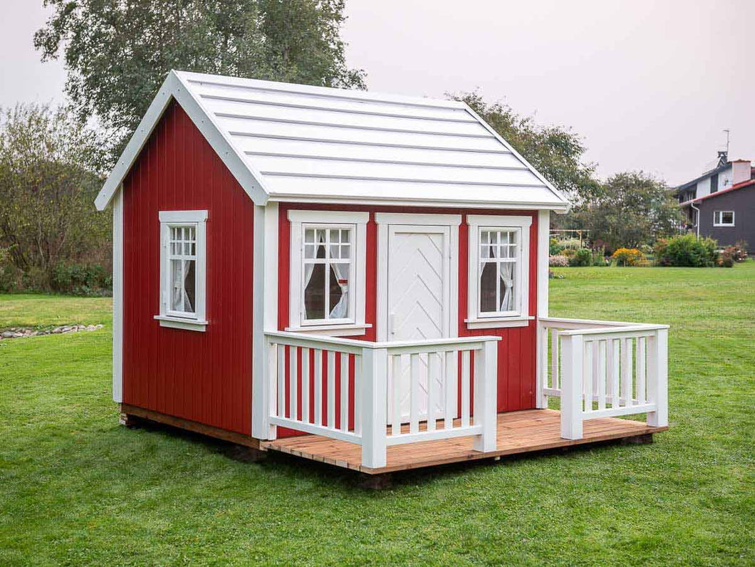 Red Outdoor Playhouse Nordic Nario with white roof, wooden terrace and white wooden fence on green lawn by WholeWoodPlayhouses