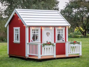 Red Outdoor Kids Playhouse Nordic Nario with white door and wooden terrace in a backyard by WholeWoodPlayhouses