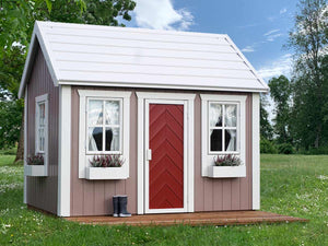 Kids Playhouse Plum with  red door, flower boxes and terrace in a backyard by WholeWoodPlayhouses
