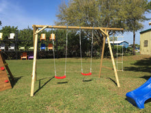 Load image into Gallery viewer, Outdoors kids swingset Magnus by WholeWoodPlayhouses with two swings and a rope ladder on a sunny day on green grass