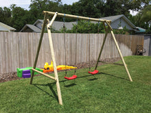 Load image into Gallery viewer, Mathias swing set with two swings for kids produced by WholeWoodPlayhouses on a sunny day on green grass in front of wooden fence