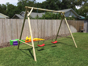 Mathias swing set with two swings for kids produced by WholeWoodPlayhouses on a sunny day on green grass in front of wooden fence