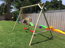 Load image into Gallery viewer, Side view of kids swing set Mathias with two swings by WholeWoodPlayhouses on a sunny day on green grass
