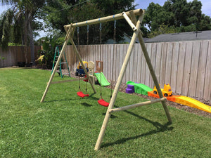 Side view of kids swing set Mathias with two swings by WholeWoodPlayhouses on a sunny day on green grass