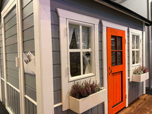 Load image into Gallery viewer, Close up of the front windows and red door of Outdoor Playhouse Boy Cave by WholeWoodPlayhouses