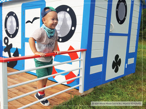 Boy on the terrace of indoor playhouse Marine Max by WholeWoodPlayhouses