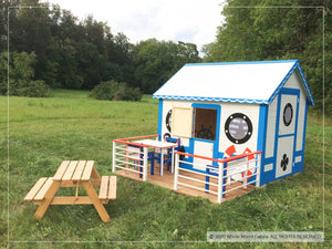 Sailing themed kids playhouse Marine Max by WholeWoodPlayhouses with a terrace and a bench on a green meadow