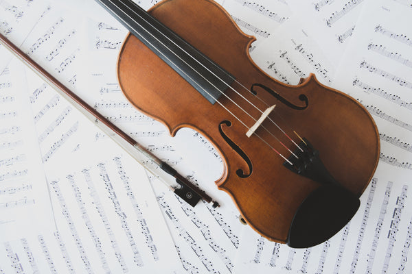 A violin and a bow on music sheets