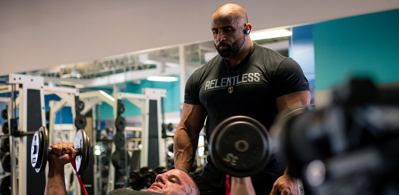 Bodybuilder Fouad Abiad spotting another bodybuilder doing dumbbell flyes