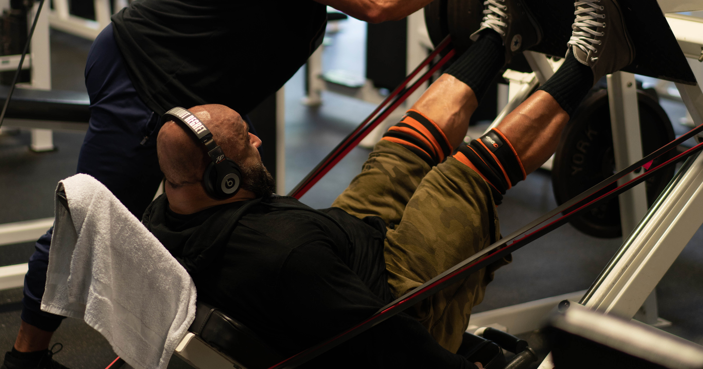 Bodybuilder Fouad Abiad doing leg presses on the leg press machine with weights and with resistance bands