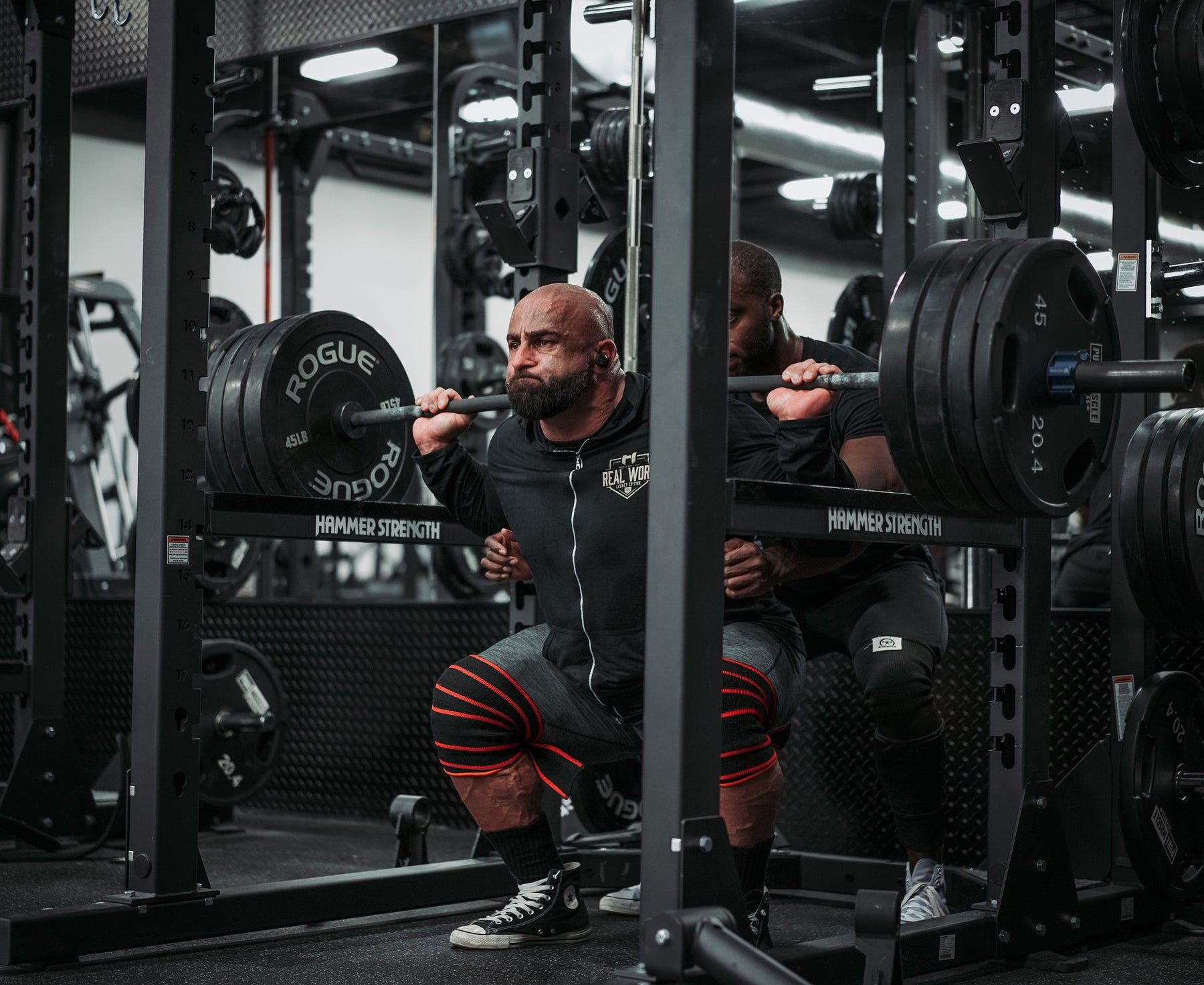 Bodybuilder Fouad Abiad squatting heavy weight in a squat rack