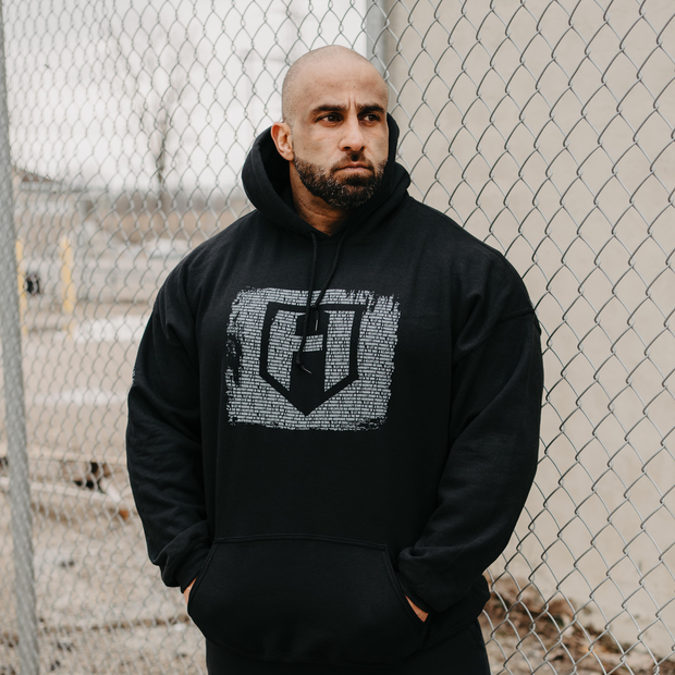 Bodybuilder Fouad Abiad standign in front of a fence wearing a Dark Knight hoodie