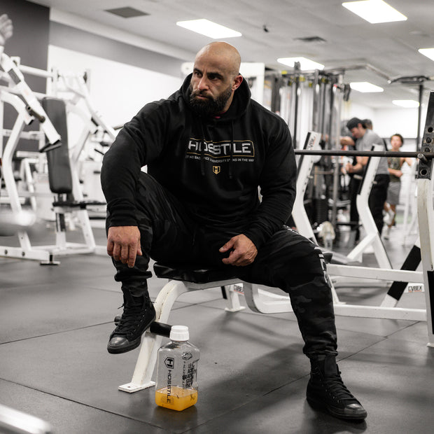 Bodybuilder Fouad Abiad wearing Hosstile Signature Hoodie sitting on a bench in the gym
